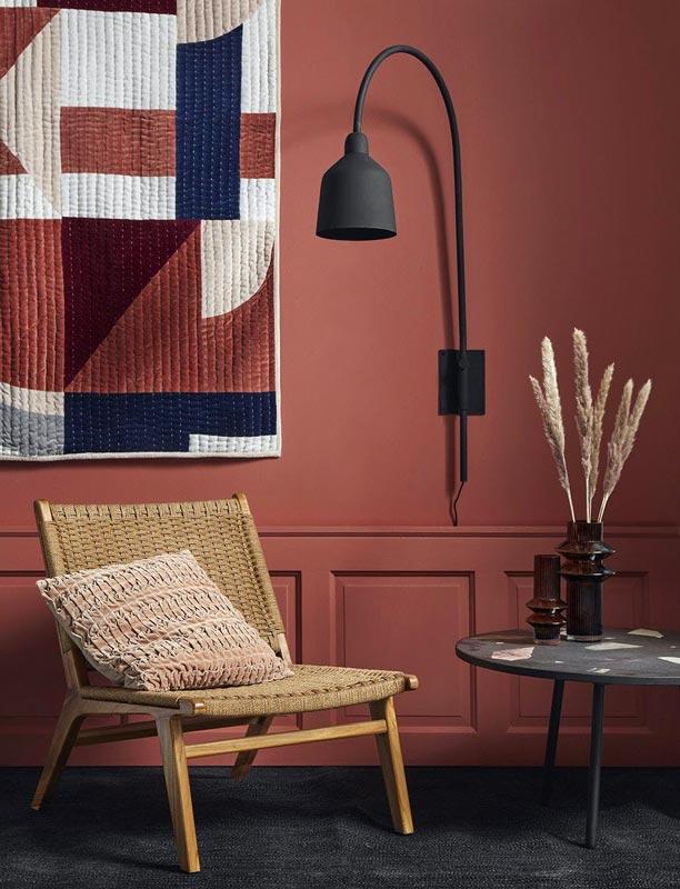 Mur peint en terracotta avec du mobilier en bois et un tapis de mur géométrique