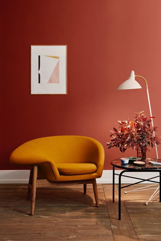 Un mur peint en terracotta derrière un fauteuil jaune moutarde