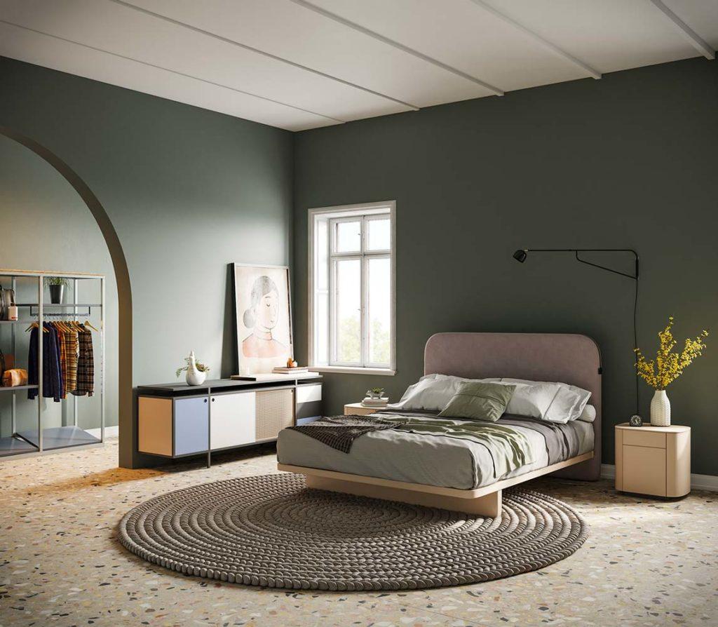 Une chambre rétro avec un sol en terrazzo beige, un mur vert sauge et du mobilier de couleur pastel