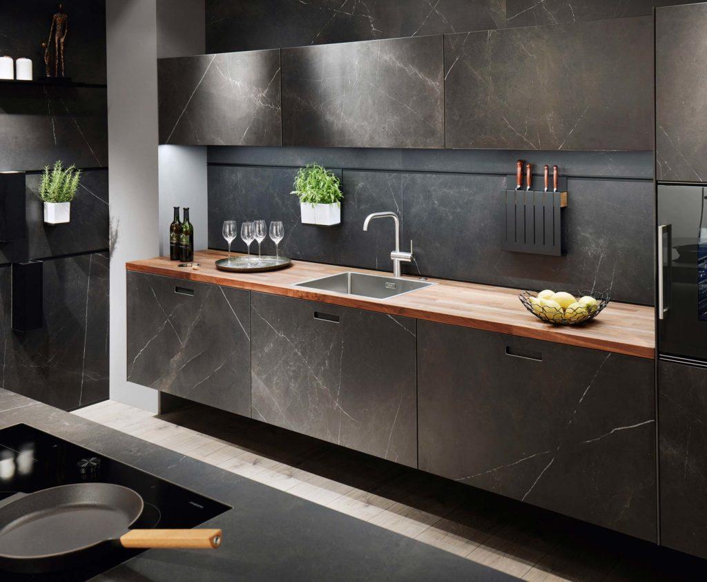 Une cuisine contemporaine en marbre noir avec un plan de travail en bois exotique