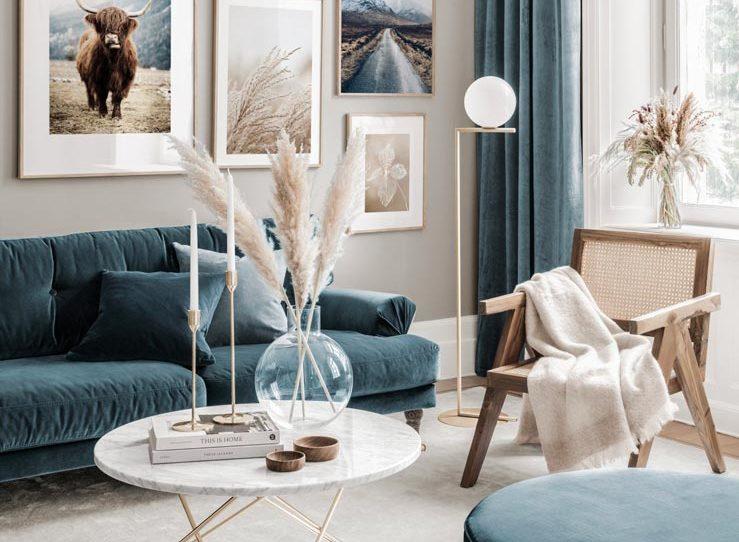 salon beige, canapé en velours bleu, fauteuil en cannage et fleurs séchées
