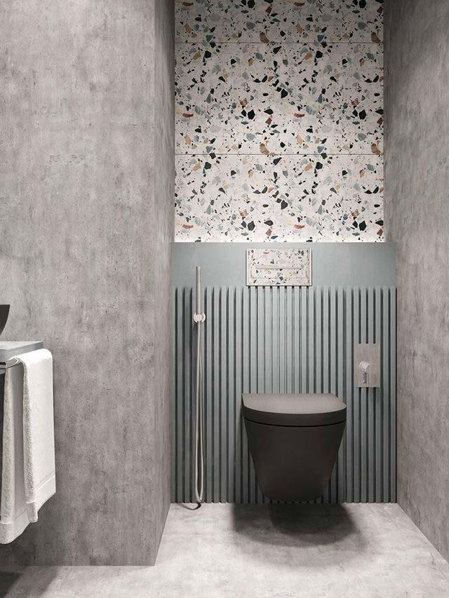 Des toilettes contemporaines avec du mur en béton ciré et un pan de mur en terrazzo graphique