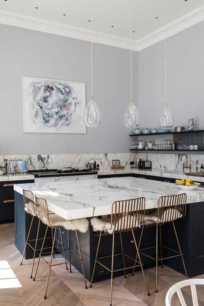 Un grand ilot central en marbre blanc avec des meubles de cuisine noir pour créer un contraste