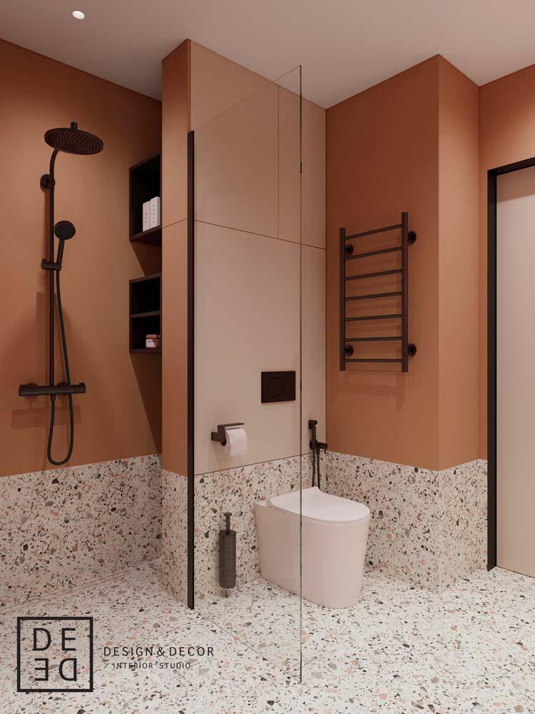 Salle de bain design de couleur terracotta, sol en terrazzo et robinetterie noire