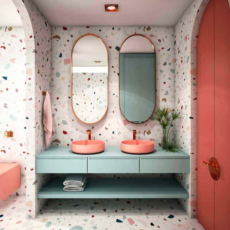 Une salle de bain vintage mouchetée de terrazzo en total look, mobilier vert sauge, vasques terracotta et miroirs ovales