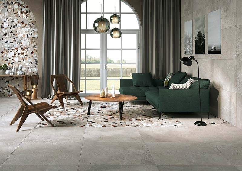 Un salon vintage avec un sol incrusté de terrazzo, un canapé en velours vert un des assises en bois exotique