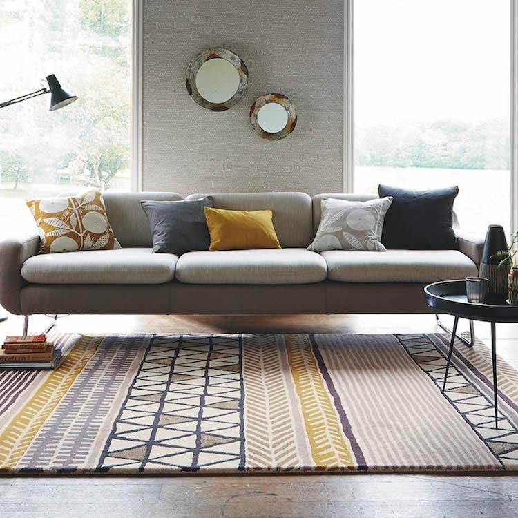 Un salon ethnique gris avec un canapé Ultimate gray, des coussins jaune et un tapis aux motifs jaune Illuminating