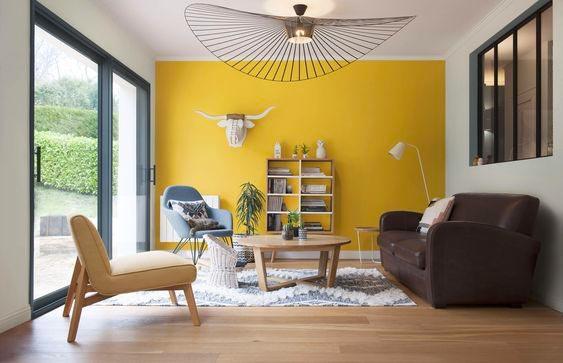 Un salon lumineux avec un pan de mur jaune illuminating