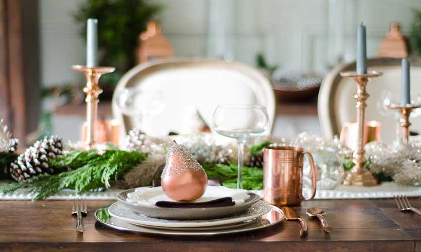 Table de Noël, centre de table en laine, assiettes blanches, bougeoirs et verres cuivrés