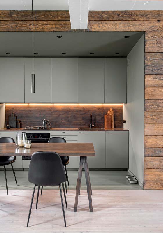 Une cuisine moderne et minimaliste kaki avec une crédence en bois
