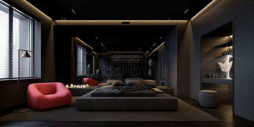 Une chambre total look noire avec un fauteuil rouge et un coin bureau