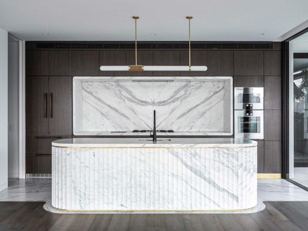 un ilot central en marbre blanc de forme ovale arrondi pour plus de convivialité