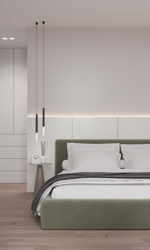 Un lit en velours kaki dans une chambre blanche