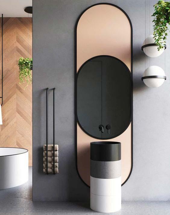 Meuble de salle de bain minimaliste tout en rondeur associé à un miroir ovale et des luminaires circulaires.