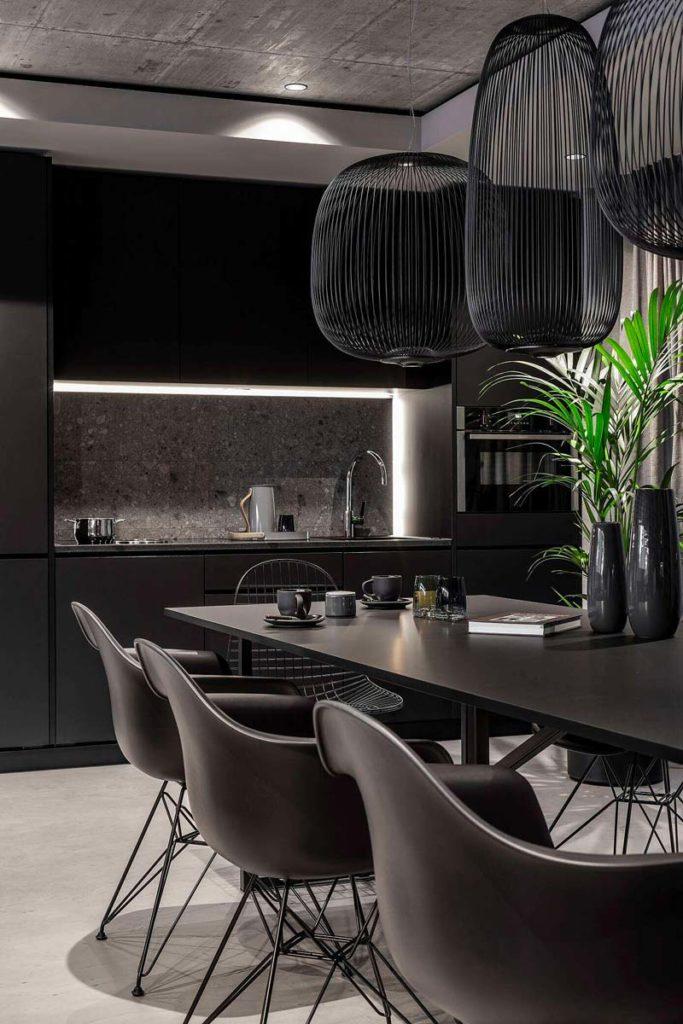 Une salle à manger foncée avec une crédence en terrazzo et du mobilier noir