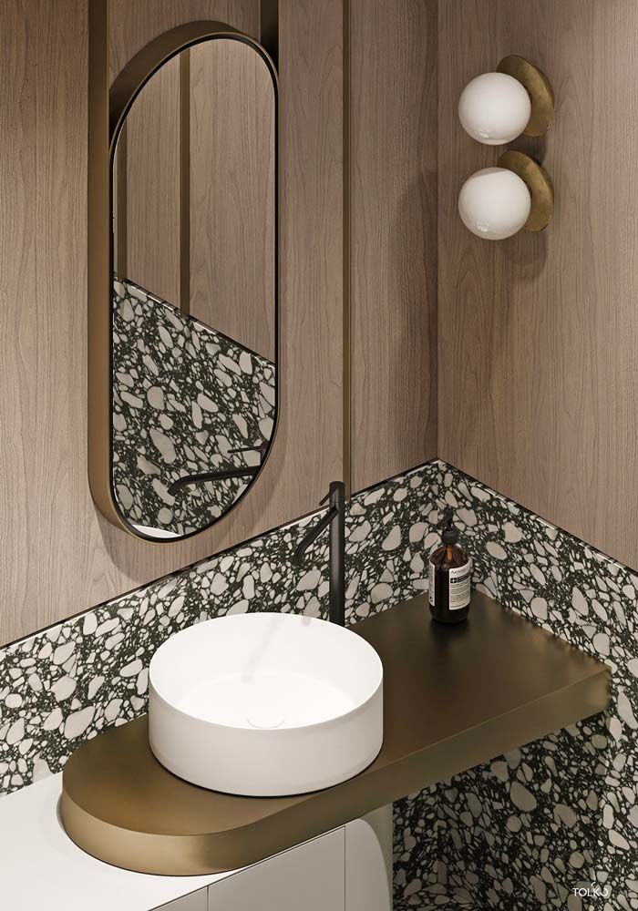 Salle de bain en terrazzo et bois clair avec vasque ronde, miroir oval et luminaire circulaire