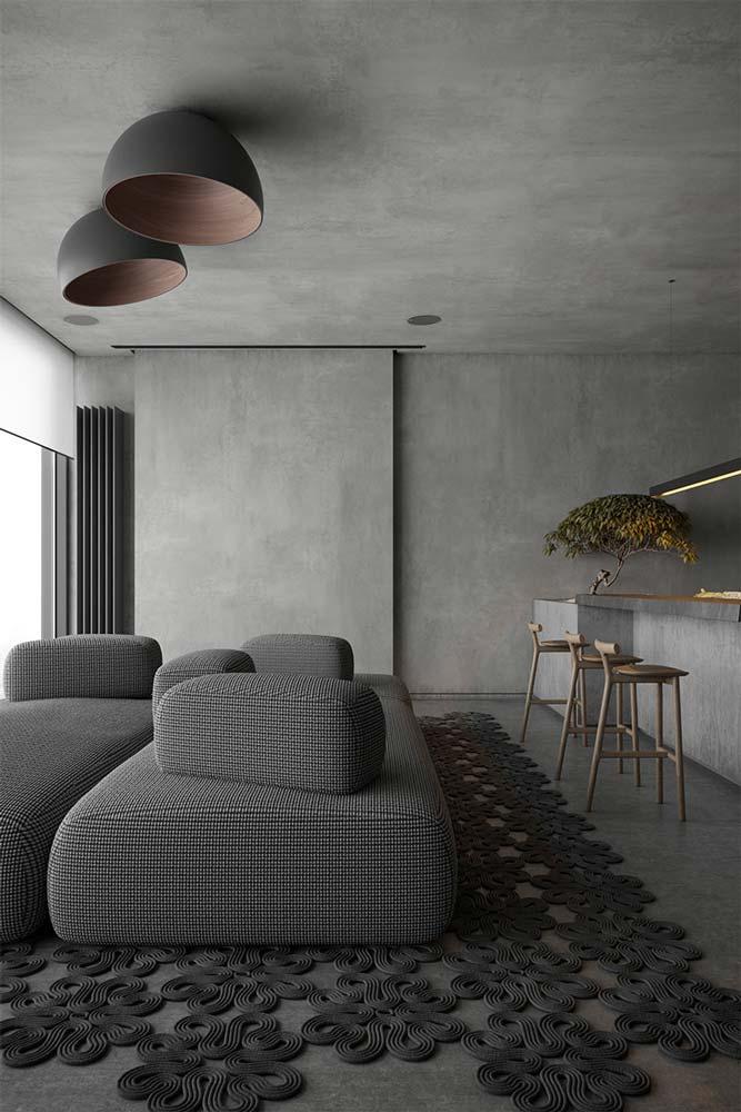Salon minimaliste et contemporain avec du mobilier rond, murs et plafond en béton brut