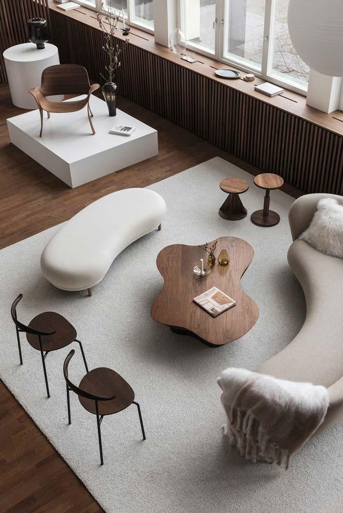 Salon ultra moderne avec canapé et fauteuils arrondis, chaises en bois aux formes incurvée et table basse en bois chaleureux de forme organique