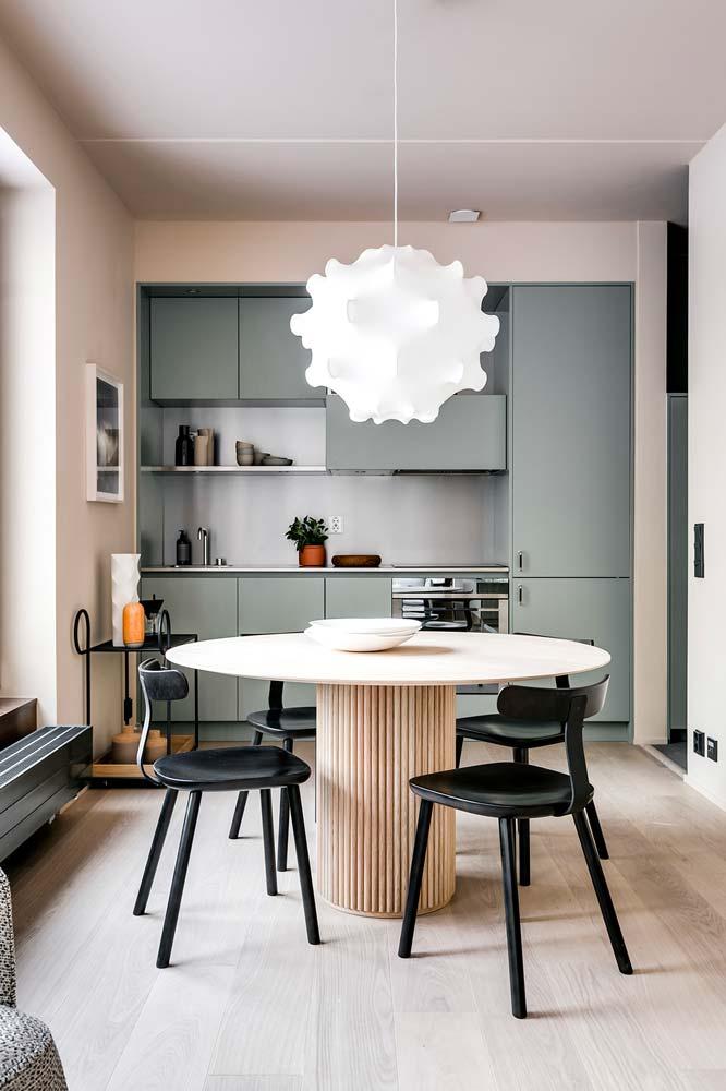 Une table de cuisine ronde en bois clair avec piétement en relief
