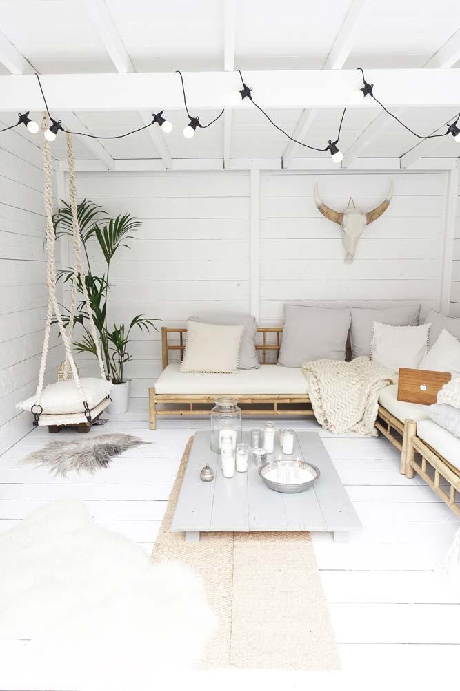 Un salon extérieur couvert tout blanc avec du mobilier en bambou