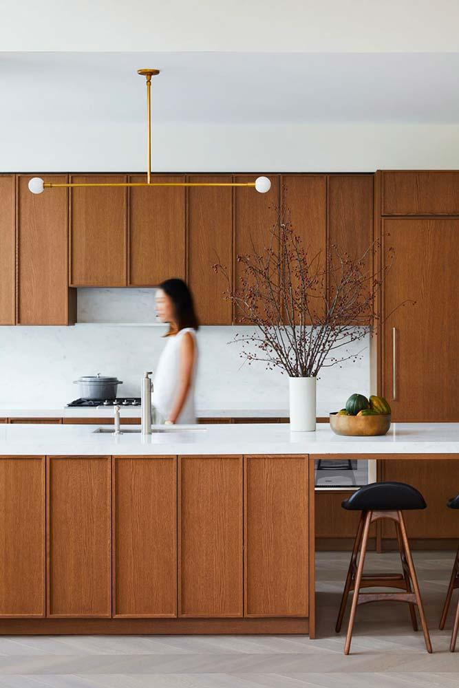 une cuisine Japandi au sol clair avec mobilier en bois brun et plan de travail blanc
