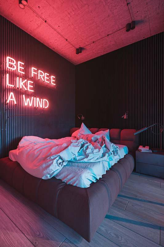 Une chambre parentale industrielle éclairé d'un néon avec une phrase rose