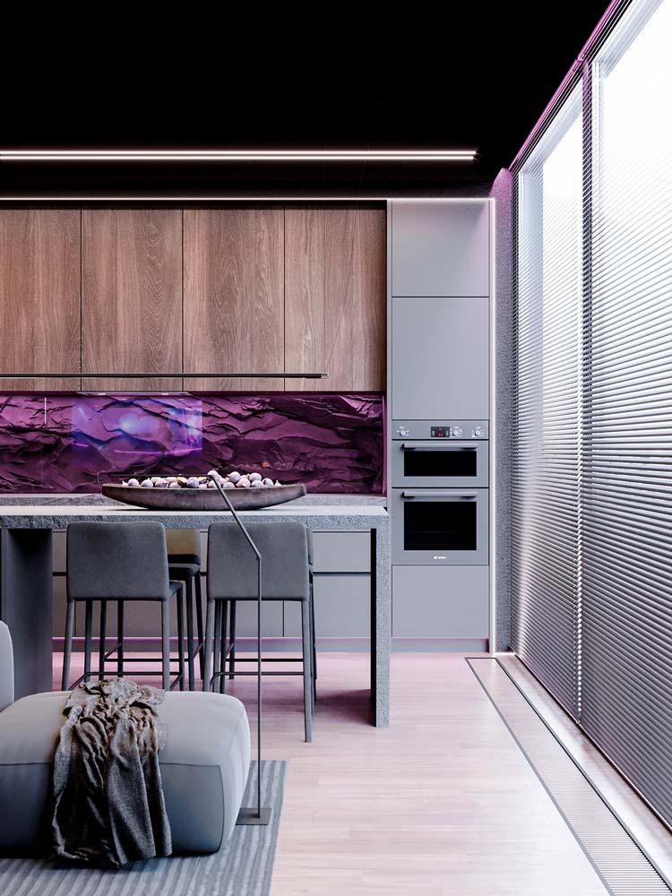 Une crédence de cuisine en roche noire éclairée par des néons violets
