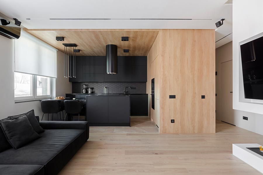 Une cuisine noire mise en valeur par une boite en plywood