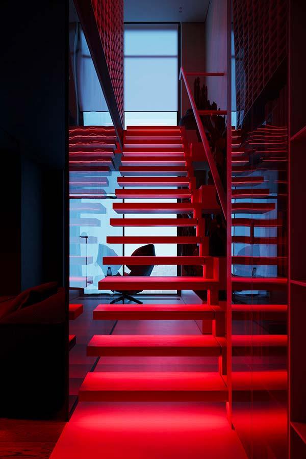 Les marches d'un escalier éclairées par des néons rouge