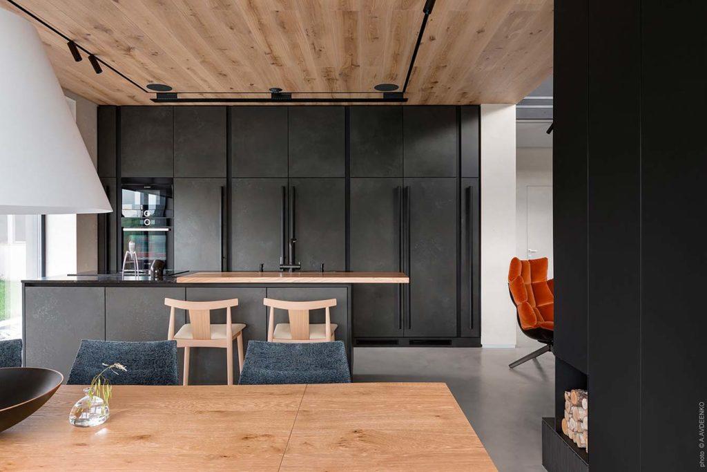 Une cuisine noire avec un bardage intérieur en chêne clair en plafond