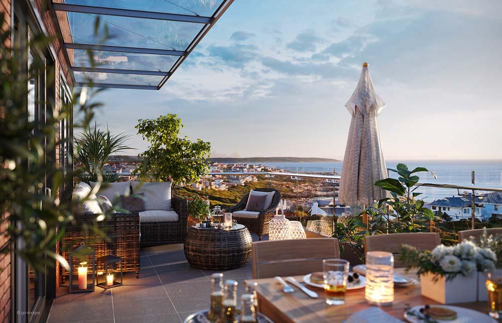 Du mobilier en osier pour un espace salon et un espace repas sur un grand balcon avec une belle vue