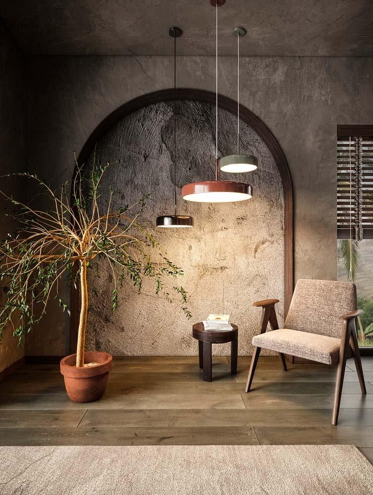 Un coin lecture avec un bout de mur en pierre, une plante en pot et un plancher en bois avec des lumières vives