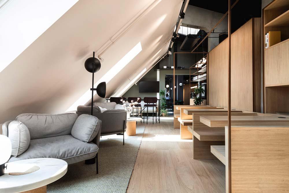 Un espace de travail avec des tables et des fauteuils en sous-pente