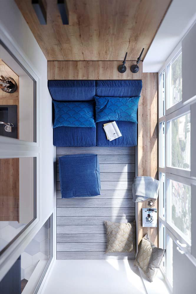 Balcon fermé agencé sur-mesure avec du bois clair et une banquette bleu roi