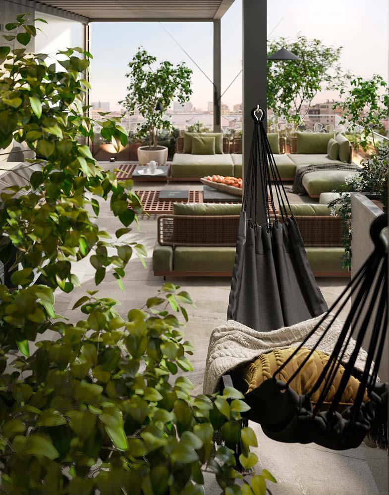 Un hamac noir et de la végétation sur un grand balcon terrasse avec du mobilier en osier et couleur kaki
