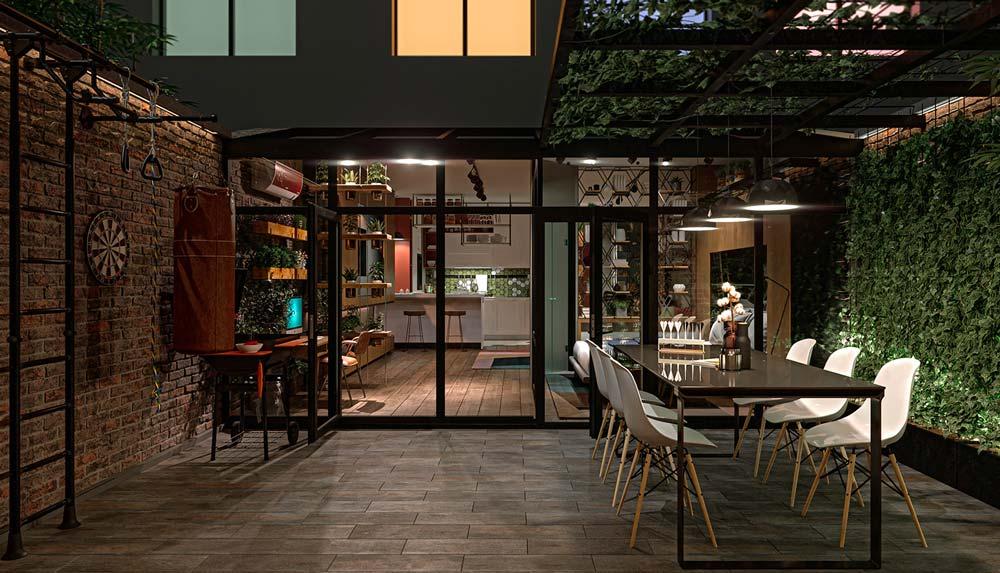 Une terrasse extérieure avec un coin musculation près d'un mur en briques et une table pour recevoir près d'un mur végétal