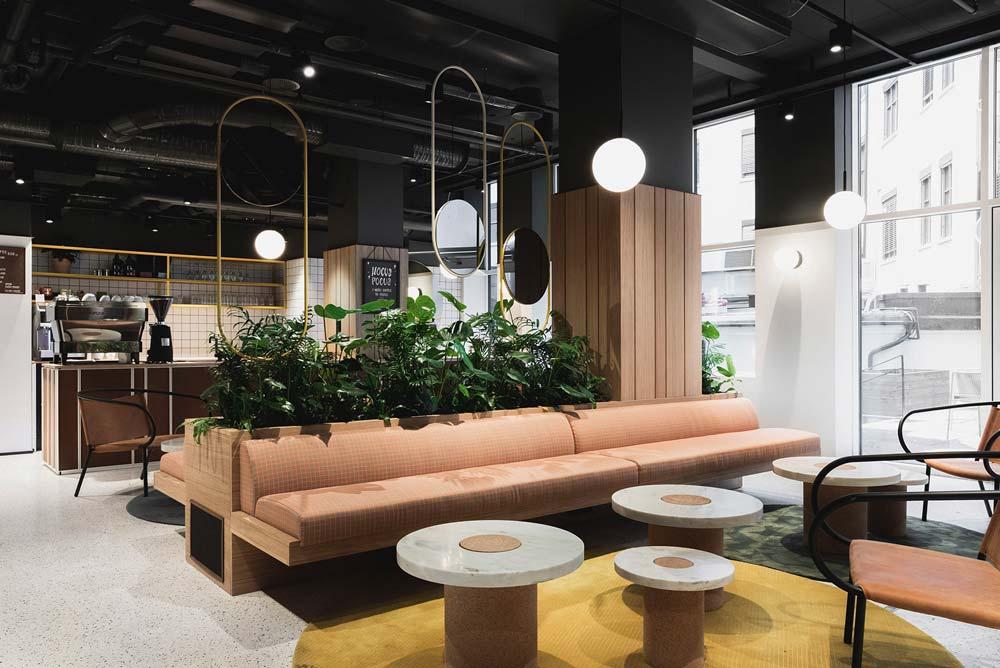 Une cafétéria lumineuse avec des banquettes et des tables basses, des plantes et un tapis jaune