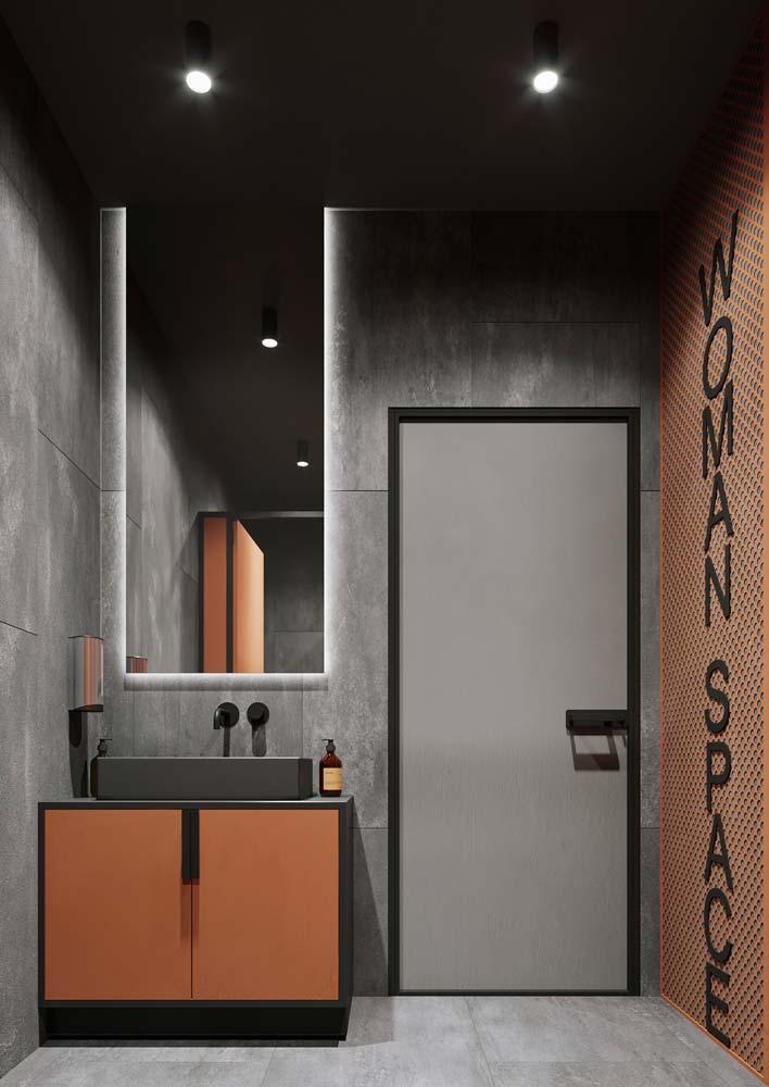 Toilettes d'un siège social au mur et sol gris et un grand miroir au-dessus du lavabo