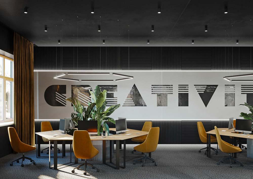 Un open space décoré avec des plantes, des fauteuils colorés, une écriture au mur et des tables hexagonales