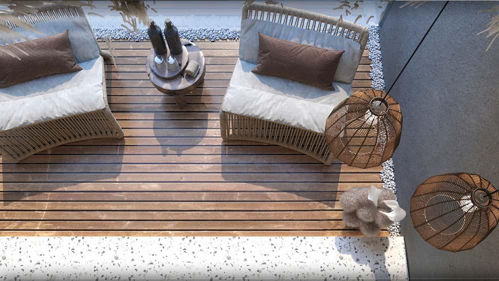 Un balcon inspiration bord de mer avec une terrasse en bois, des fauteuils en osier et un sol en terrazzo clair