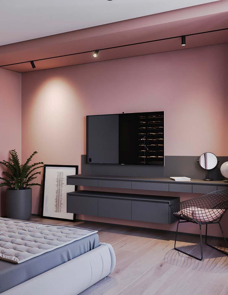 Une chambre parentale avec un plancher clair et un renfoncement mural couleur vieux rose avec du mobilier gris