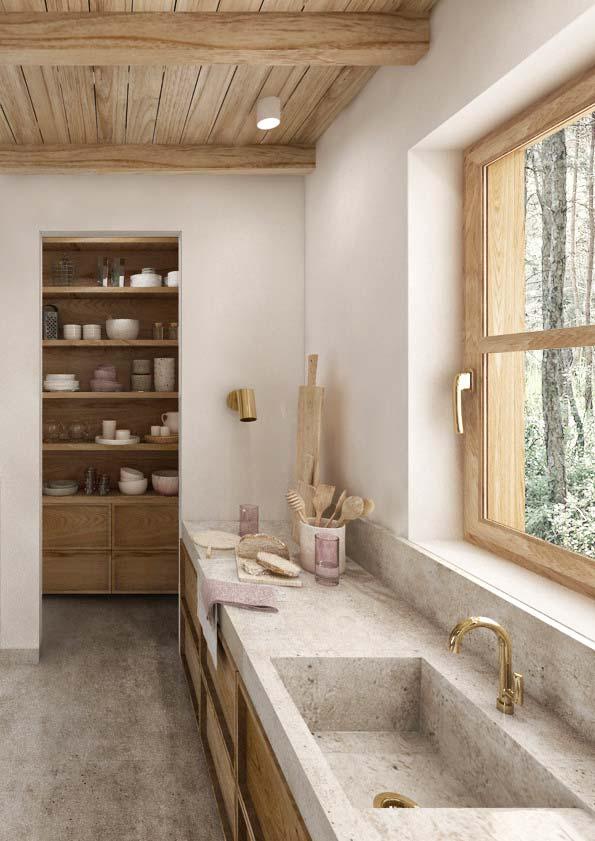 Une cuisine campagne chic en bois blonc et en pierre avec des murs blancs et de la robinetterie dorée