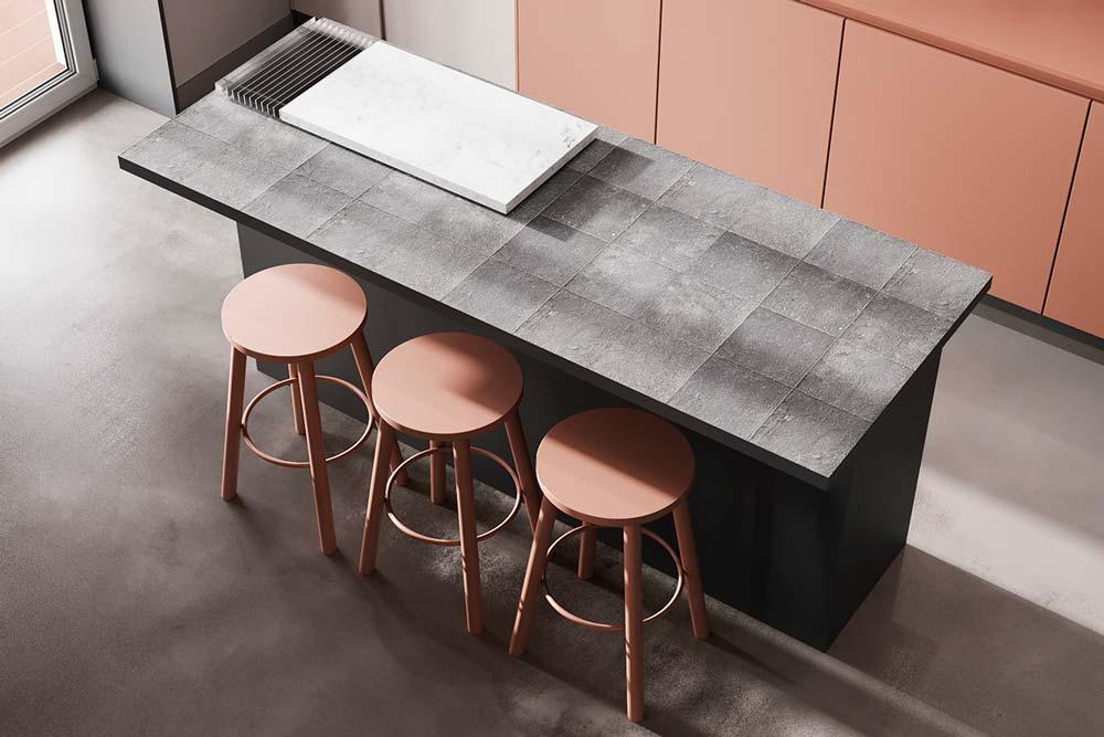 Une cuisine moderne minimaliste avec des placards et tabourets en vieux rose et un sol en béton