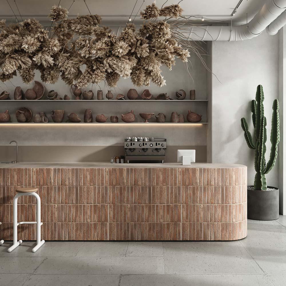 Un îlot de cuisine en carrelage rectangulaire avec de la déco en poteries et une suspension de fleurs séchés