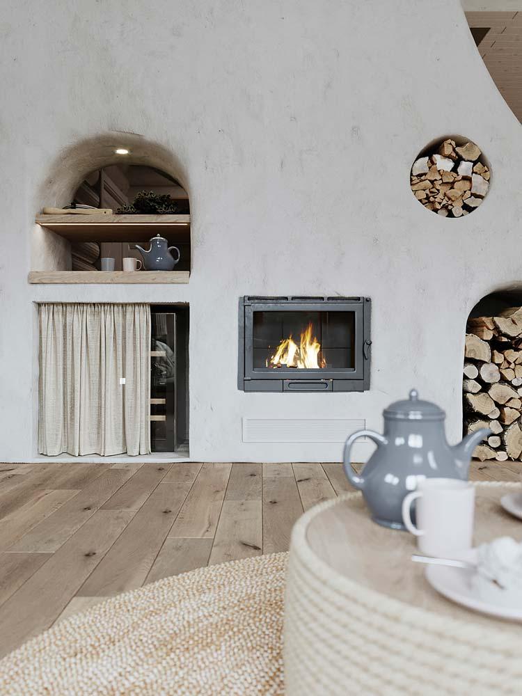 Un salon campagne chic avec un mur blanc simple, plancher en bois et table basse en corde avec quelques accessoires déco en bois et porcelaine