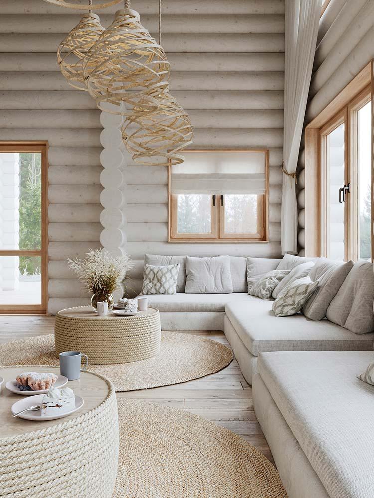 Un salon campagne chic avec du bois, des tables basses en corde, des tapis en jute et un grand canapé d'angle clair