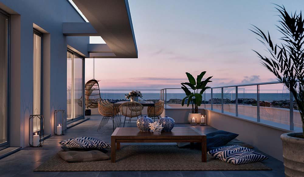 Un grand balcon zen et cocooning avvec des coussins autour d'une table basse et des sièges en osier avec un fauteuil suspendu