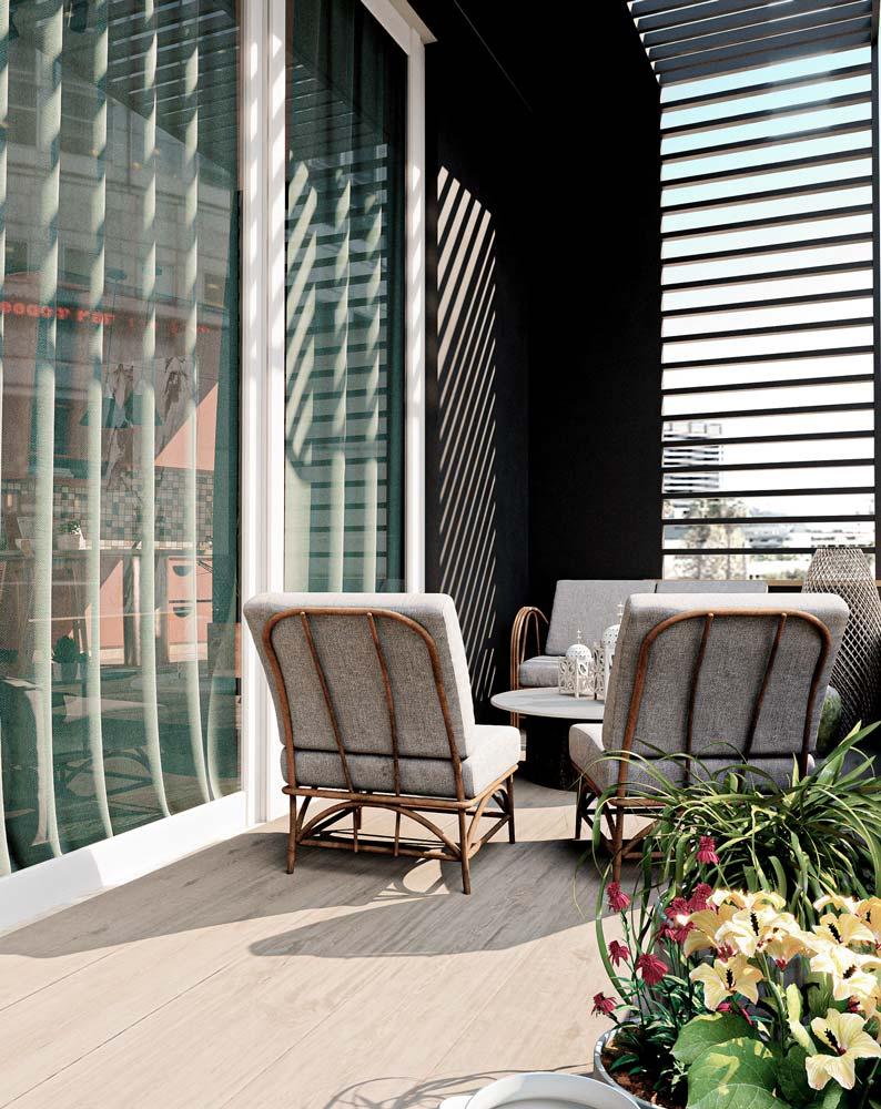 Un petit salon extérieur sur un balcon au parquet clair avec des assises confortables gris et osier