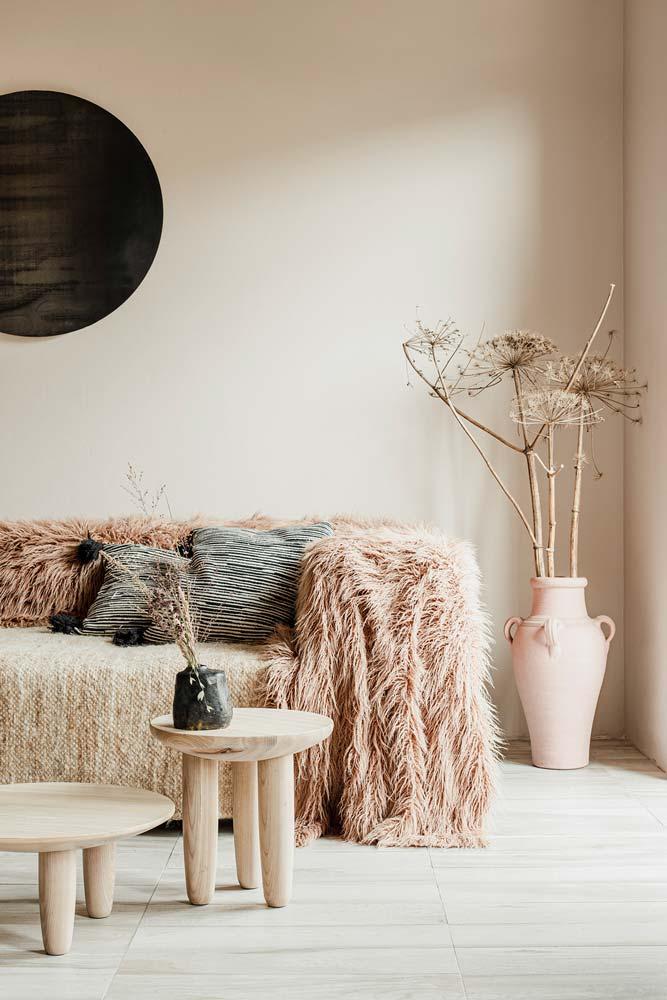 Des coussins et couvertures sur un canapé slow design dans un salon avec un pot en argile