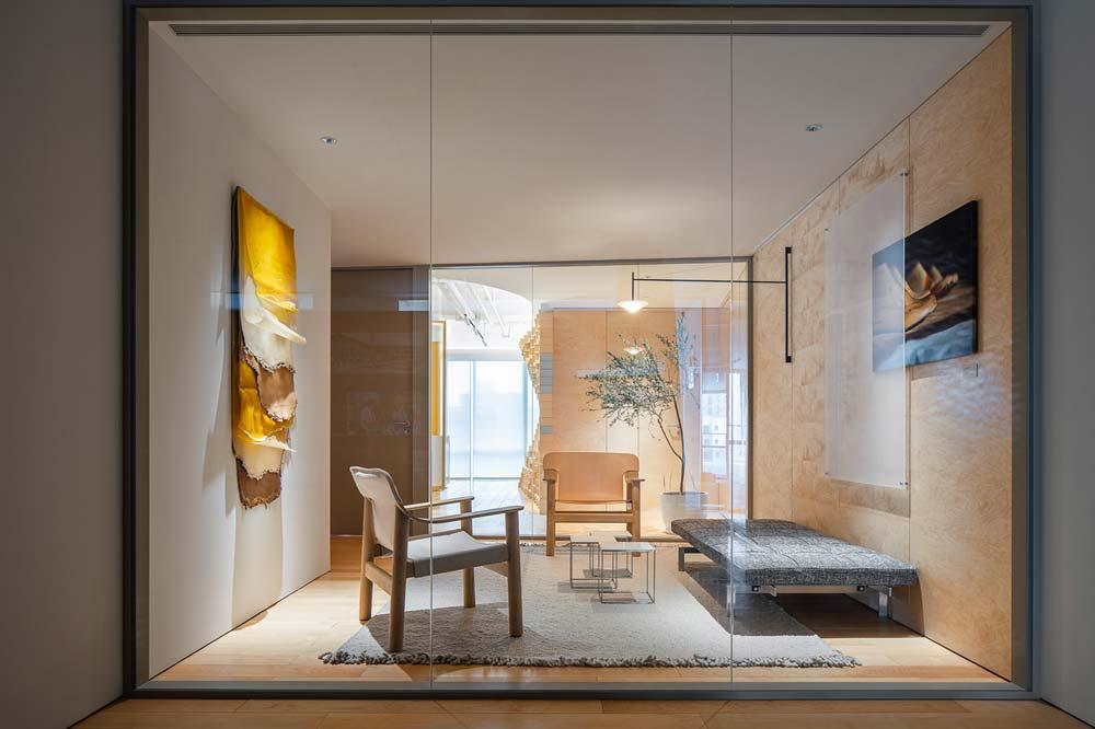 Salle de réunion vitrée avec sièges, banquette, mur en bois et un tapis gris